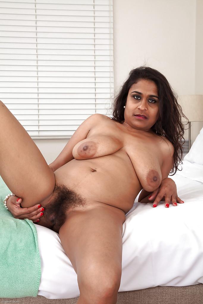 Взрослая барышня снимает лифчик в постели и светит лохматую пизду порно фото